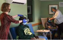 Carry Berryman fits the goggle headset on the resident at senior communities.